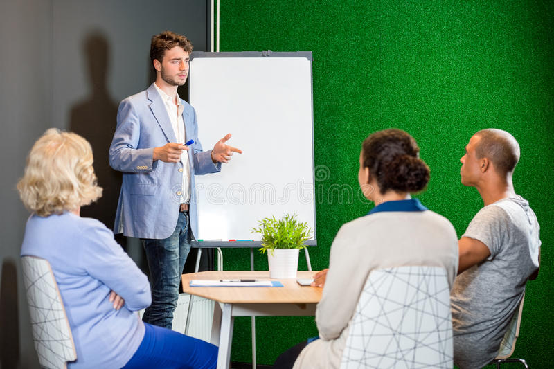 AffärsmanGiving Presentation To kollegor arkivfoto