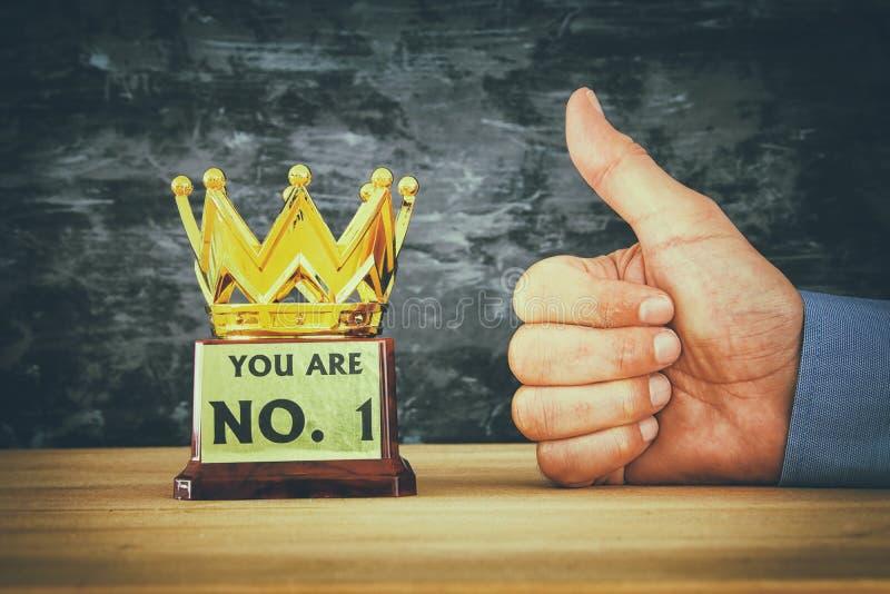 Affärsmanhand bredvid utmärkelsetrofén för seger eller att segra för show det första stället royaltyfri fotografi
