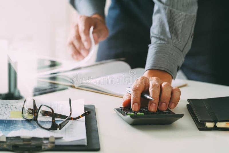 affärsmanhand som arbetar med finanser om kostnad och räknemaskinen arkivfoto