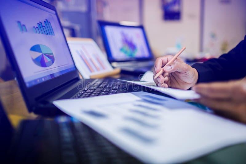 Affärsmanhand som arbetar på bärbar datordatoren med diagrammet för information om affärsgraf på träskrivbordet royaltyfri fotografi