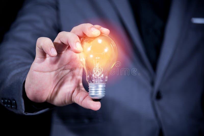 Affärsmanhand som rymmer concep för ljus kula, idé- och teknologi arkivbilder