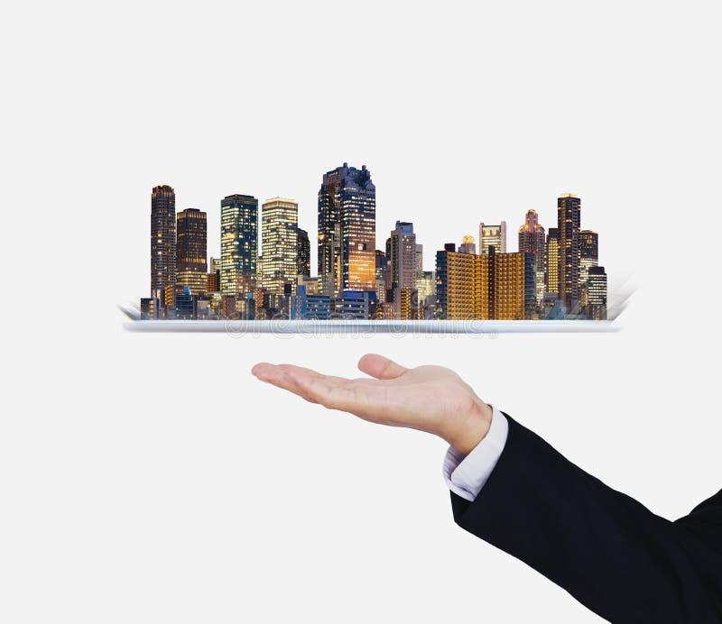 Affärsmanhand som rymmer den digitala minnestavlan med det moderna byggnadshologrammet Smart stad, byggnadsteknologi och fastighe royaltyfri fotografi