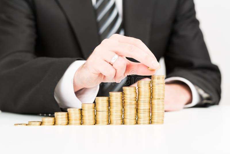 Affärsmanhand som sätter växande affär för pengarmyntbunt arkivfoton