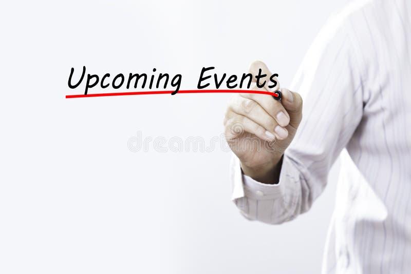 Affärsmanhand som skriver kommande händelser, affärsidé royaltyfri foto