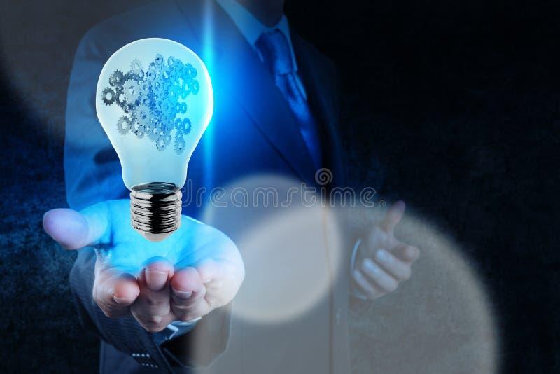Affärsmanhand som visar den ljusa kulan med kugghjul arkivbilder