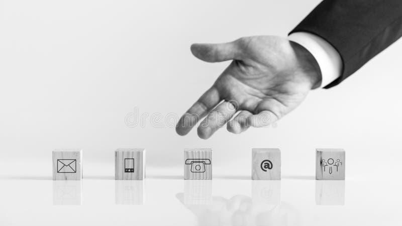 Affärsmanhand som visar träkvarter med kontaktsymboler royaltyfri fotografi