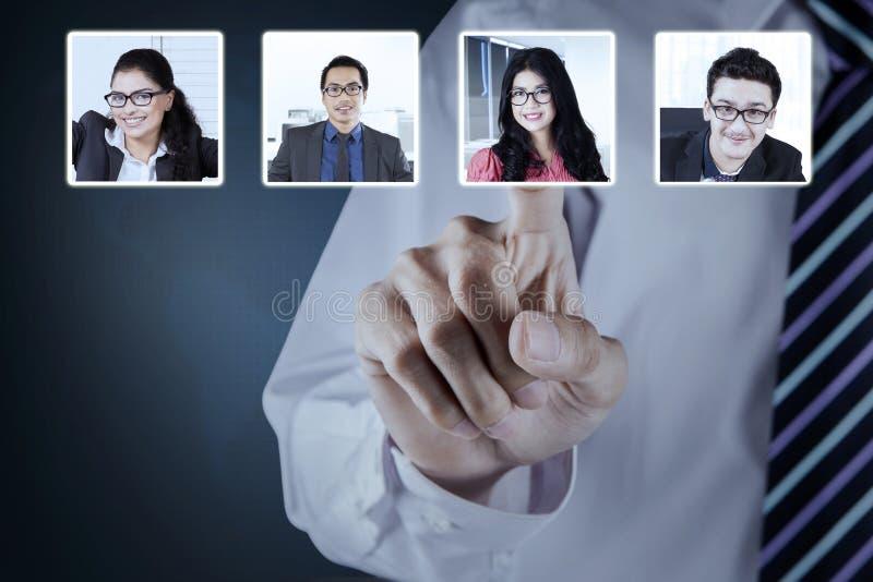 Affärsmanhanden väljer partnern på den faktiska skärmen royaltyfri fotografi