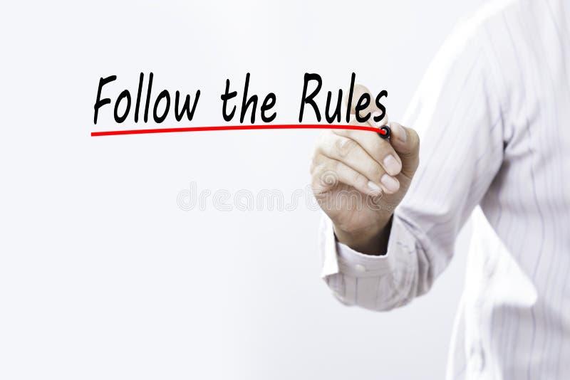 Affärsmanhandhandstil följer reglerna med den röda markören på tra arkivfoto