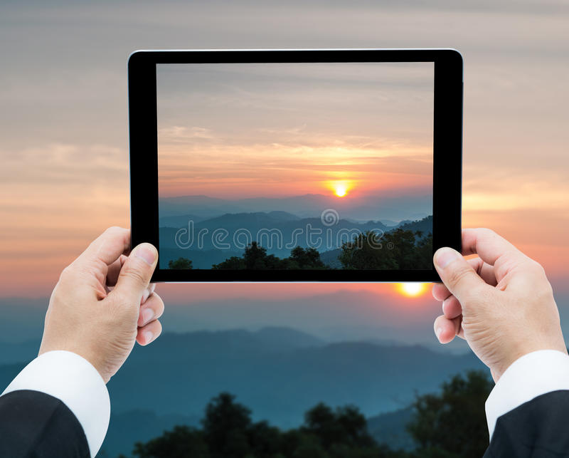 Affärsmanhandminnestavla som tar bilder majestätisk solnedgång i arkivbilder