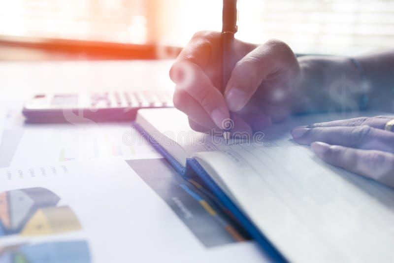 Affärsmanhandstil på anteckningsboken på trätabellen, folk antecknar redovisningsdata som beräknas från en räknemaskin royaltyfri bild