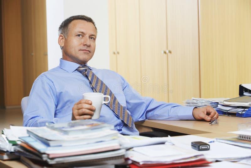 AffärsmanHaving Coffee At skrivbord arkivfoton