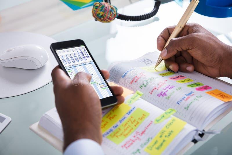 AffärsmanHolding Cellphone Writing schema i dagbok royaltyfri foto