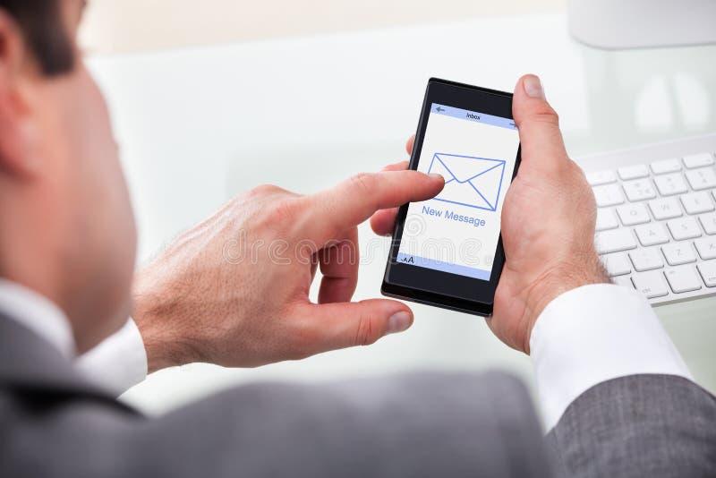 AffärsmanHolding Mobile With nytt meddelande på en skärm arkivbilder