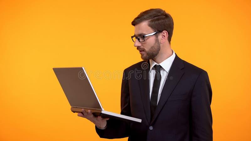 Aff?rsmaninnehavb?rbar dator i handen, l?sningemail som kontrollerar nytt programvaruarbete royaltyfri fotografi