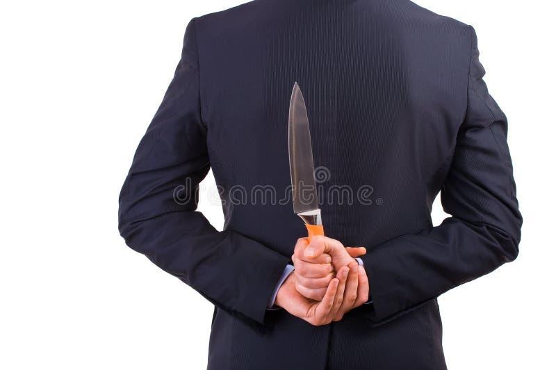 Affärsmaninnehavkniv bak hans baksida. arkivbild