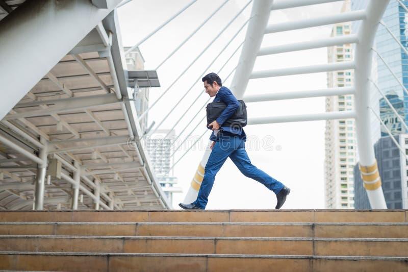 Affärsmaninnehavpåse och spring snabbt i staden begrepp av rusningstiden och sent för arbete arkivfoton