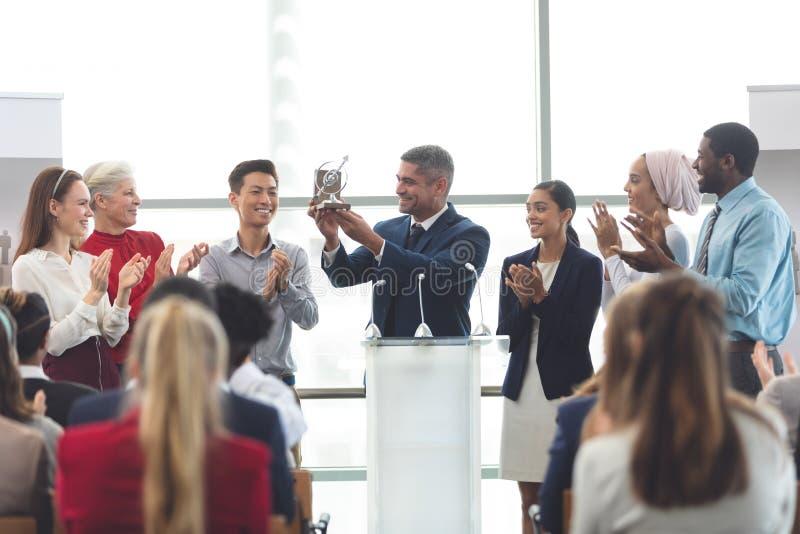 Affärsmaninnehavutmärkelse på podiet med kollegor i ett affärsseminarium royaltyfria bilder