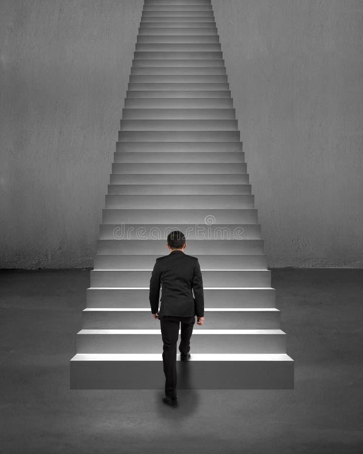 Affärsmanklättring för bakre sikt på trappa med fläckbelysning royaltyfri foto