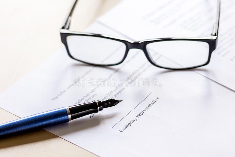 Affärsmankontorsskrivbord med avtalet för signig, exponeringsglas och penna royaltyfri fotografi