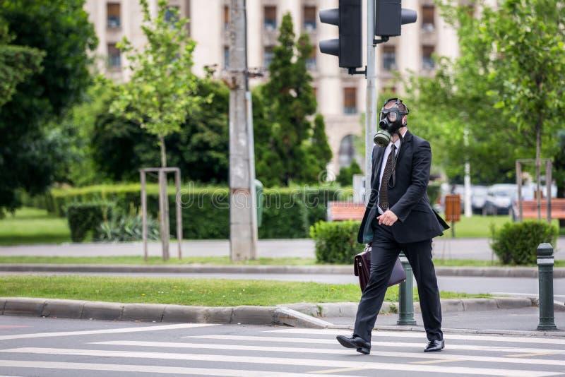 Affärsmankors den utomhus- gatan bära en gasmask på framsidan royaltyfri bild