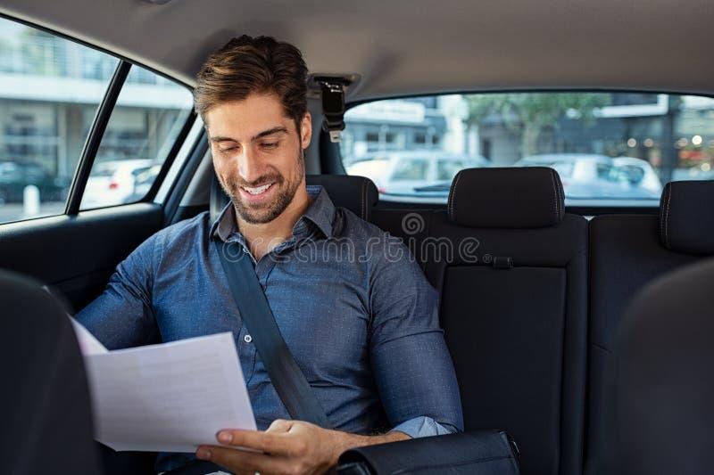 Affärsmanläsningdokument i bil arkivfoto