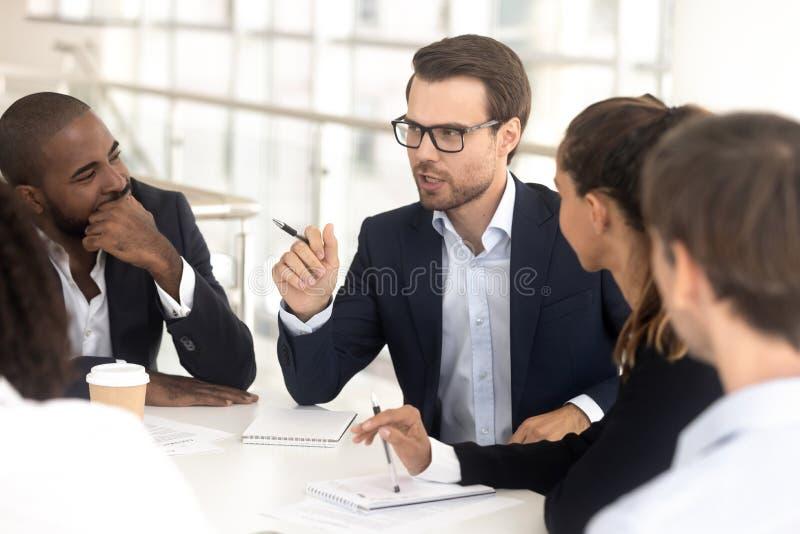 Affärsmanlagledare som talar på gruppmötet som förhandlar diskutera nytt projekt arkivbild