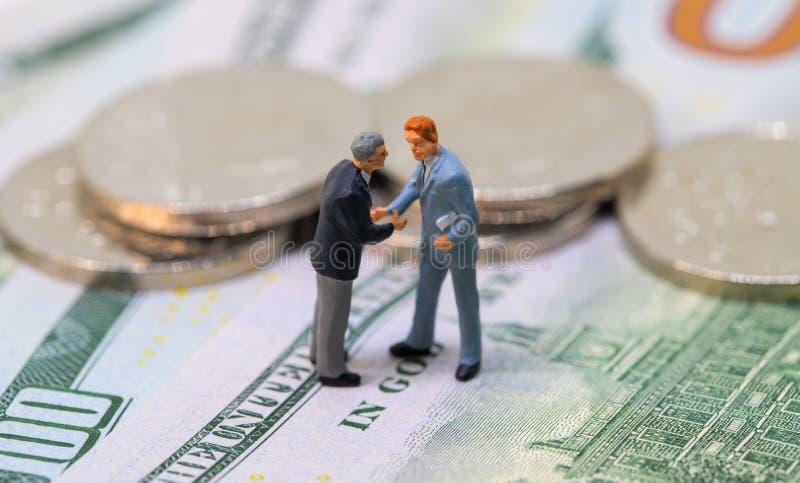 Affärsmanleksak som skakar händer på kassa Mycket små affärsmanstatyetter på pengarbakgrund fotografering för bildbyråer