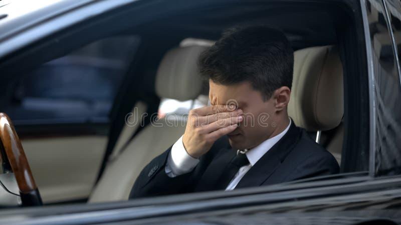 Affärsmanlidandehuvudvärk som är trött efter stressat arbete, brist av sjukvården royaltyfria bilder