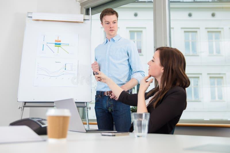 AffärsmanLooking At Female Coworker som pekar på diagram royaltyfri foto
