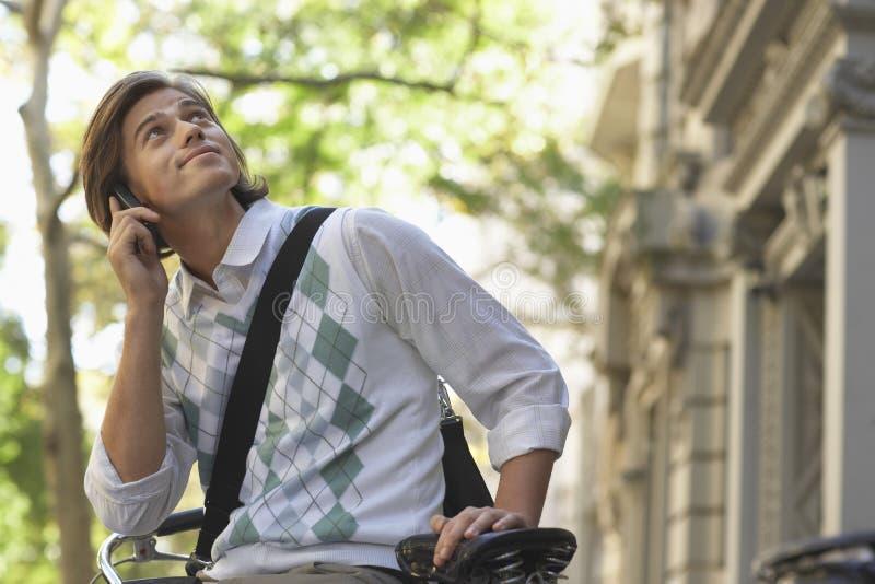 AffärsmanLooking Up While svarande påringning på cykeln fotografering för bildbyråer