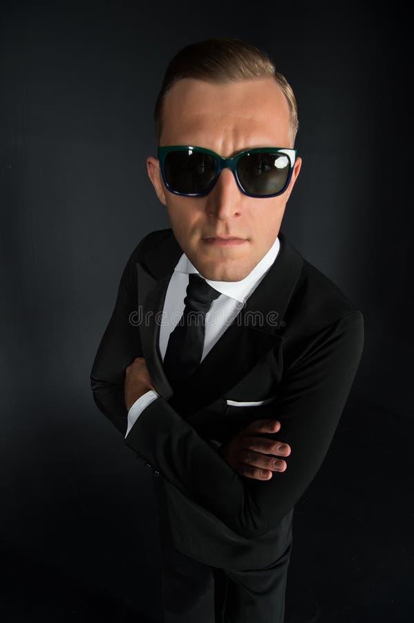 Affärsmanman i svart dräkt och solglasögon på mörk bakgrund royaltyfria foton