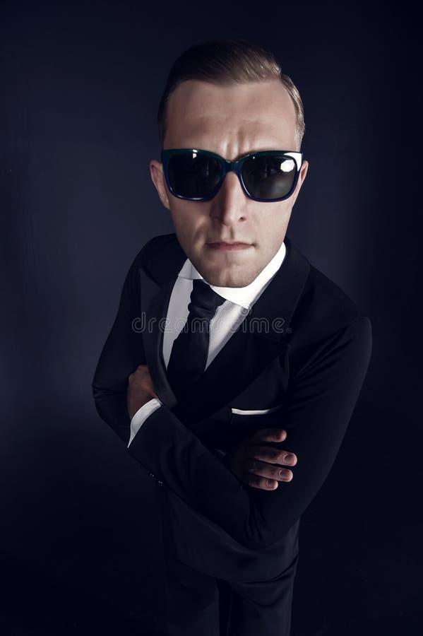 Affärsmanman i svart dräkt och solglasögon på mörk bakgrund arkivbilder