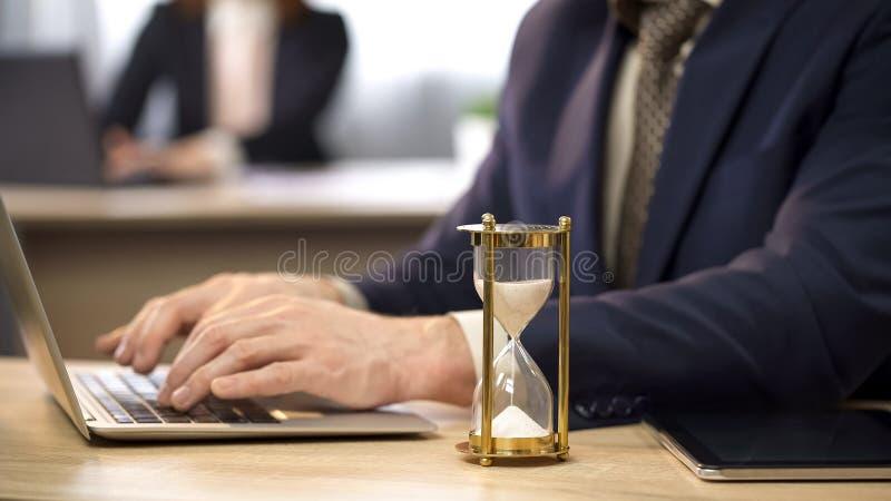 Affärsmanmaskinskrivning på bärbara datorn på skrivbordet, timglas som sipprar, att närma sig för stopptid royaltyfri bild