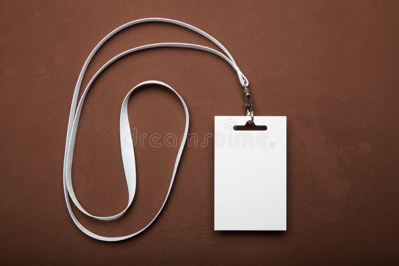 Affärsmannamnkort med taljerepet på brun bakgrund ID f?r blankt kort royaltyfria foton