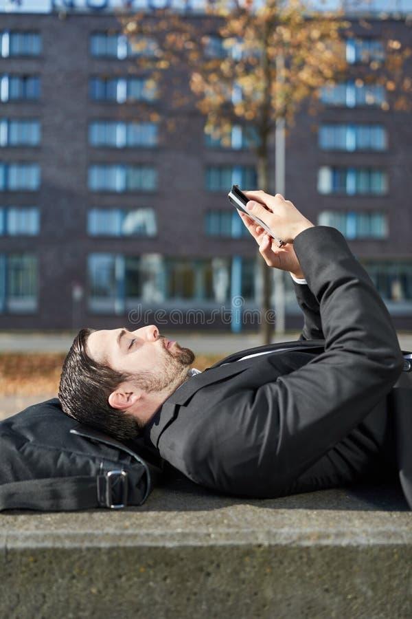 Affärsmannen använder en smartphone app arkivbilder