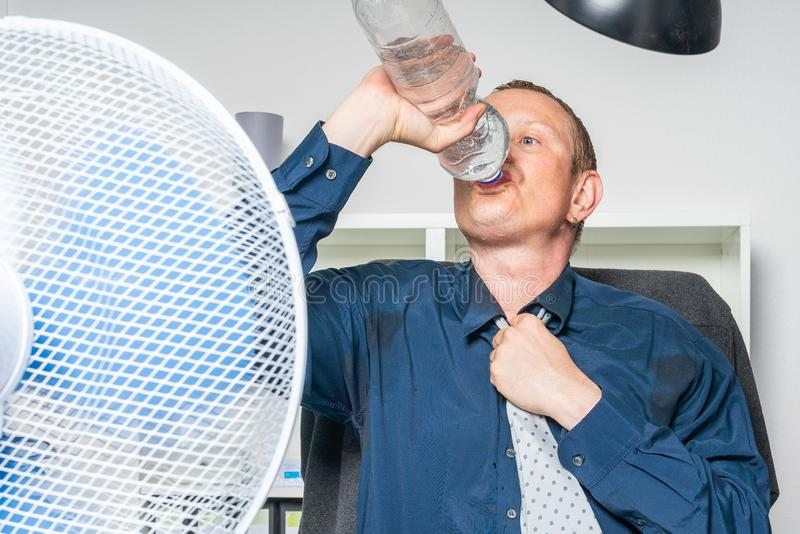 Affärsmannen arbetar i ett varmt kontor och är dricksvatten royaltyfri fotografi
