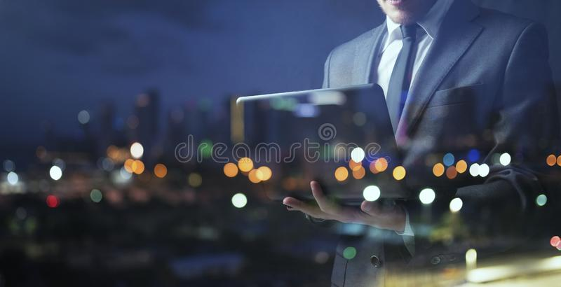 Affärsmannen arbetar med hans bärbar dator under natten dubbel exponering arkivbilder