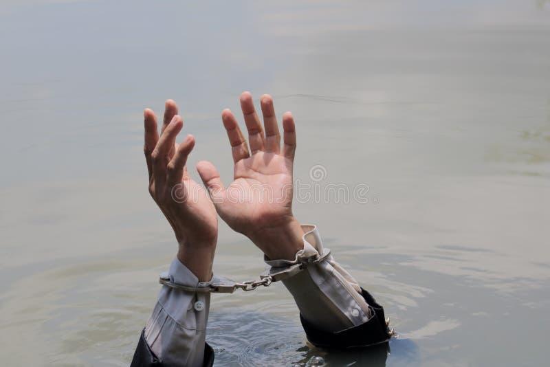 Affärsmannen arresterades av handbojor och drunkning arkivbilder