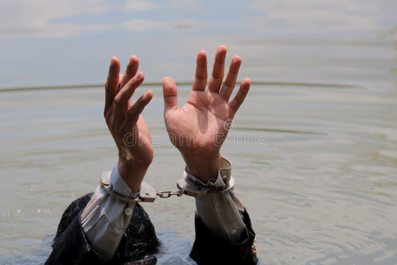 Affärsmannen arresterades av handbojor och drunkning royaltyfria bilder