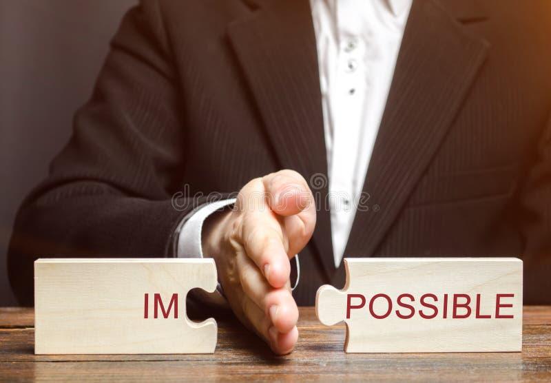 Affärsmannen avskiljer pussel med det omöjliga ordet Begreppet av själv-motivationen och prestation av mål Affär arkivfoto
