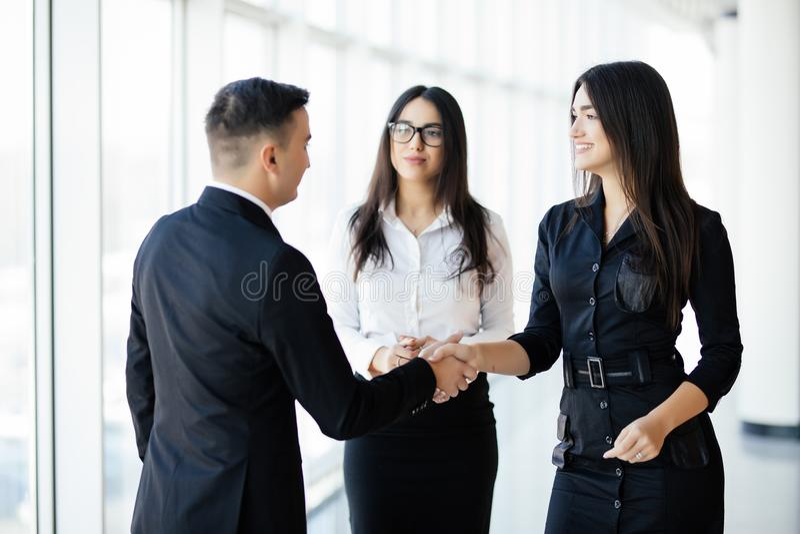 Affärsmannen And Businesswoman Shaking räcker i regeringsställning korridoren på det informella mötet arkivfoto