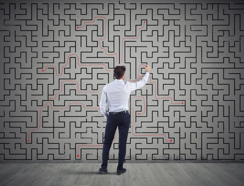 Affärsmannen drar lösningen av en labyrint Begrepp av problemlösning fotografering för bildbyråer