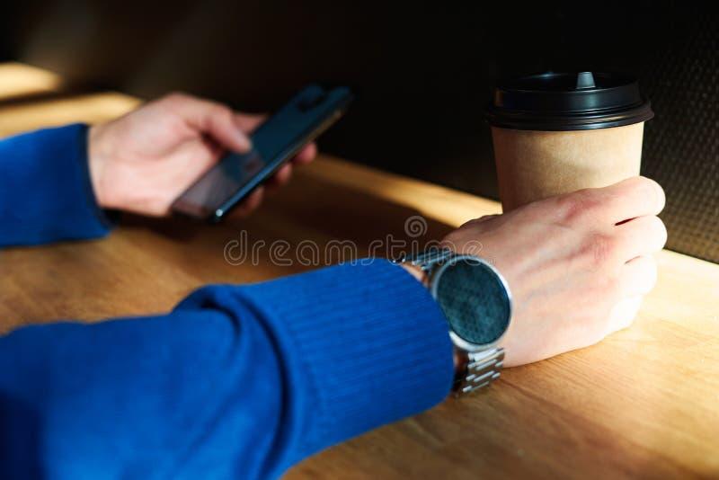 Affärsmannen dricker kaffe i ett kafé, närbild rymmer ett disponibelt pappers- exponeringsglas, genom att använda smartphonen, me royaltyfria bilder