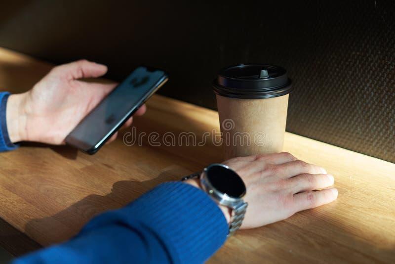 Affärsmannen dricker kaffe i ett kafé, närbild rymmer ett disponibelt pappers- exponeringsglas, genom att använda smartphonen, me fotografering för bildbyråer