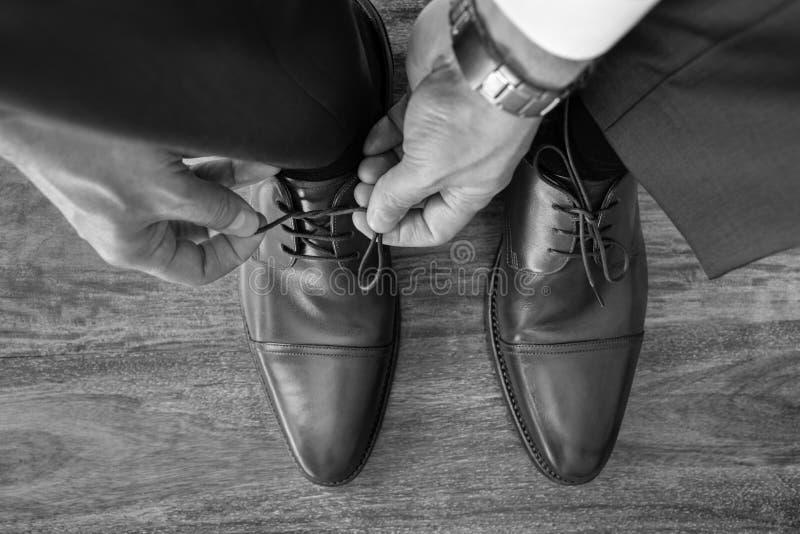 Affärsmannen eller brudgummen som binder skon, snör åt att förbereda sig arkivbilder