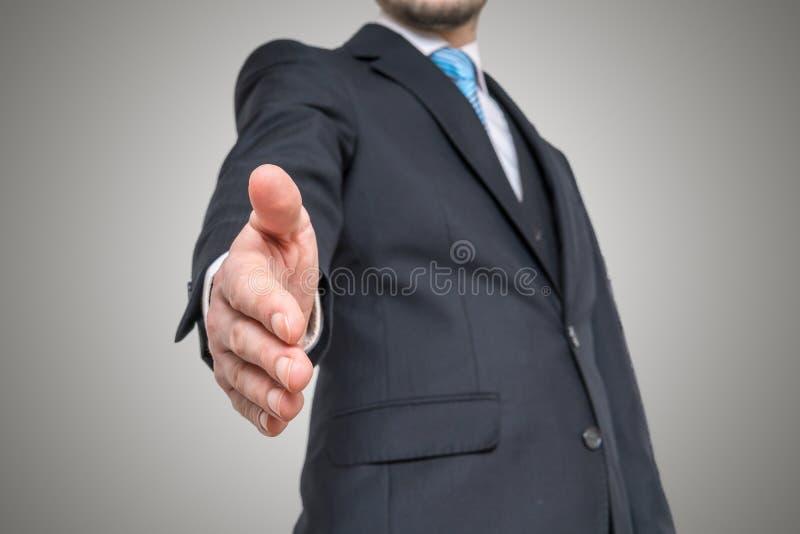 Affärsmannen erbjuder handen för handskakning Inbjudan- och avtalsbegrepp royaltyfri foto
