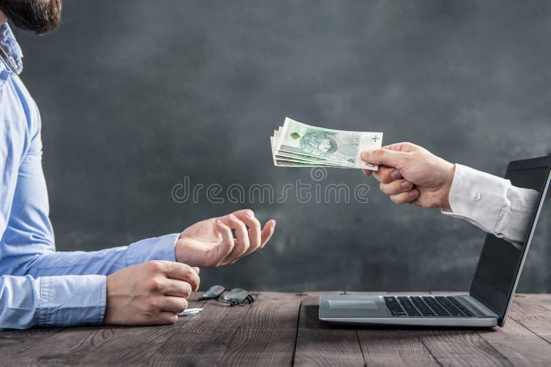 Affärsmannen får polsk kassa från handen arkivfoto