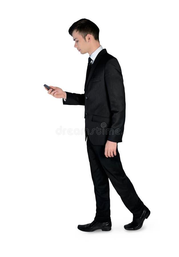 Affärsmannen går med telefonen arkivfoto