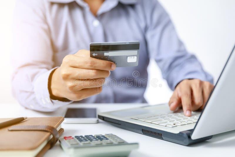 Affärsmannen gör online-shopping på datoren med kreditkorten royaltyfri bild