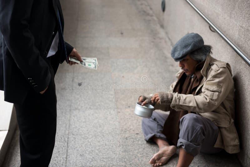 Affärsmannen ger pengar till den hemlösa mannen royaltyfri foto